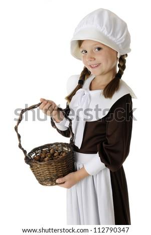 A beautiful elementary Pilgrim displaying her basketful of acorns.  On a white background. - stock photo