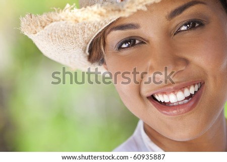 A beautiful ethnic mixed race young woman laughing and having fun wearing a straw cowboy hat, shot outside with a natural green background - stock photo