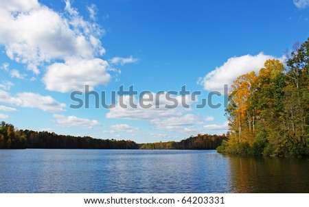 A beautiful fall water scape of Beaverdam Reservoir in Gloucester Virginia leading away to anywhere with a gorgeous sky and room for your text - stock photo