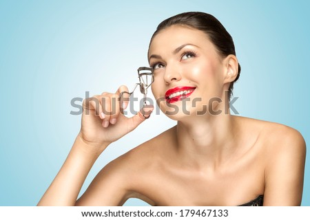 A beautiful fashion girl holding an eyelash curler in her hand as a makeup accessory. - stock photo