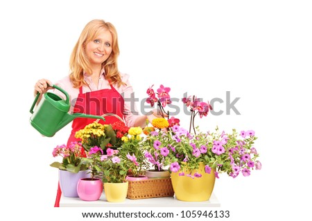 A beautiful female florist holding a can and watering flowers isolated on white background - stock photo