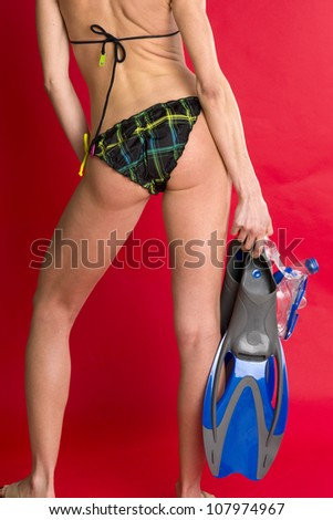 A beautiful female torso back side stands with Snorkeling Gear - stock photo
