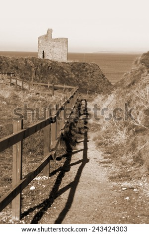 a beautiful fenced path to Ballybunion beach and castle in sepia - stock photo