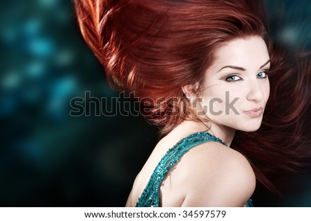 A beautiful fiery red haired woman with her hair mid movement with a blue abstract background. - stock photo