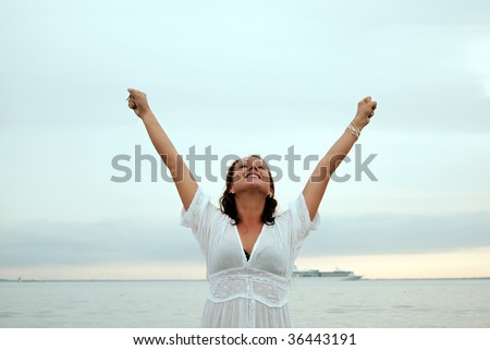A beautiful, fit and healthy young woman throws her hands in the air in a fit of joy. - stock photo