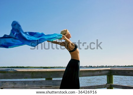 a beautiful fit woman is stretching in the sunshine, standing tall with her arms reaching out behind her with blue silk blowing in the breeze, plenty of room for copy or text - stock photo