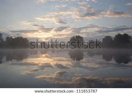 A beautiful foggy sunrise by a lake - stock photo