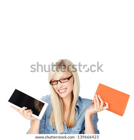 A beautiful friendly young blond woman wearing glasses holds up a printed book and e-reader in her hands as she struggles to make a decision or choice as to which is best, isolated on white - stock photo