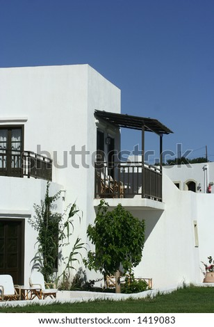 A beautiful front entrance with a balcony to a greek villa againts the bright blue sky - stock photo