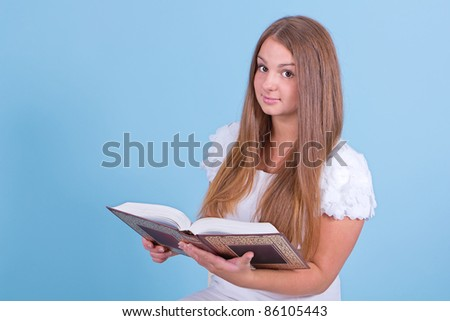 A beautiful girl dressed in a white dress reading a book - stock photo