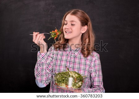 A beautiful girl eating salad on blackboard background. Healthy food concept. - stock photo