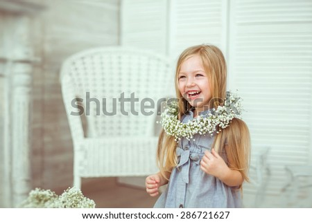 A beautiful girl is grinning all over her face. Her smile is engaging, her eyes are attractive.She is having a light blue dress and a floral wreath on. The atmosphere of happiness is all around her. - stock photo