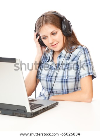 a beautiful girl is listening to the music and looking at a laptop. isolated on white background - stock photo