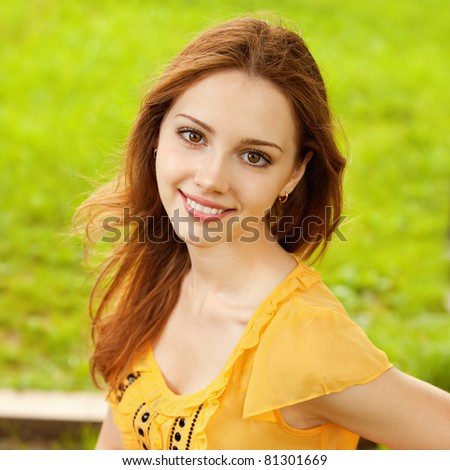 A beautiful girl is sitting on a park bench on a background of green nature - stock photo