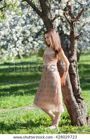A beautiful girl is walking in apple tree garden in spring time - stock photo