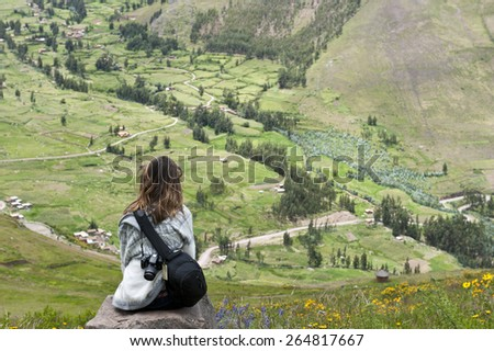 A beautiful girl looking out into the Peruvian landscape on an overcast day in the Calca Province. - stock photo