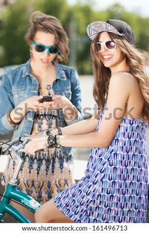 a beautiful girl smiles for the camera while her friend chats on the phone - stock photo
