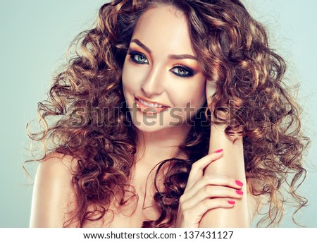 A beautiful girl with long curly hair and fashion make-up - stock photo