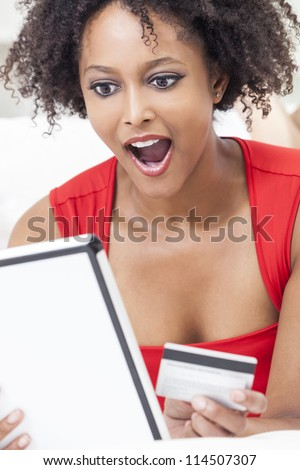 A beautiful, happy and surprised, mixed race African American girl or young woman laying down wearing a red dress using a tablet computer and credit card internet shopping on line - stock photo