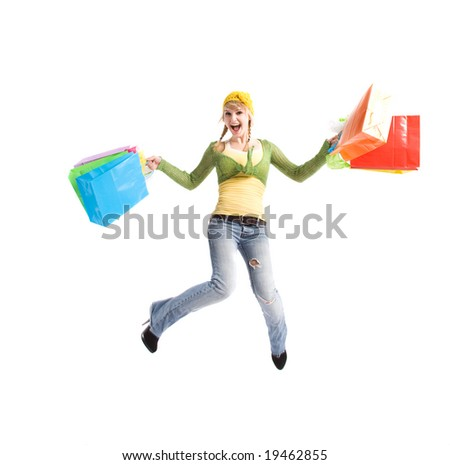 A beautiful happy caucasian girl jumping and carrying shopping bags - stock photo