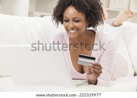A beautiful happy mixed race African American girl or young woman laying down on sofa using a laptop computer shopping on line using her credit card - stock photo