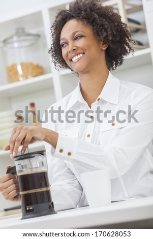 A beautiful happy mixed race African American girl or young woman making coffee with a cafetiere in her kitchen at home - stock photo