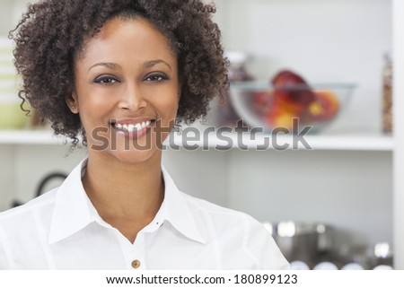 A beautiful happy mixed race African American girl or young woman using in her kitchen with fresh fruit - stock photo