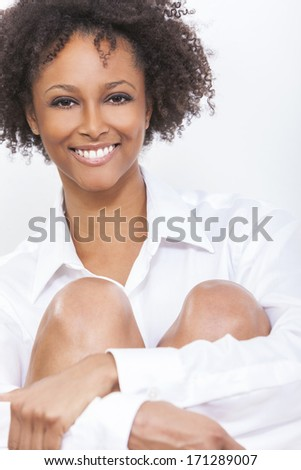 A beautiful happy mixed race African American girl or young woman wearing a white shirt smiling with perfect teeth - stock photo