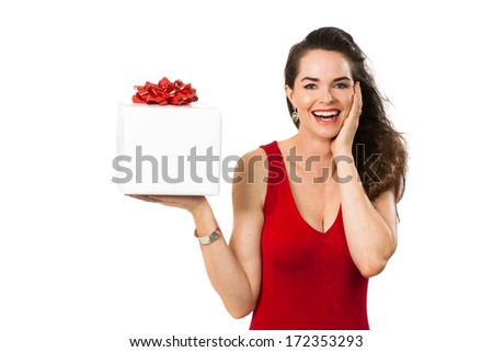 A beautiful happy surprised woman in a red dress smiling and holding a big white gift box. Isolated on white. - stock photo