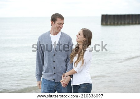 A beautiful happy young caucasian couple smiling and walking barefoot on the beach. - stock photo
