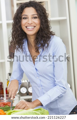 A beautiful happy young woman or girl cutting & preparing fresh vegetable salad food in her kitchen at home - stock photo