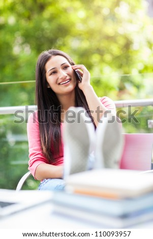 A beautiful hispanic college student talking on the phone on campus - stock photo