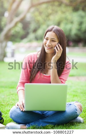 A beautiful hispanic college student talking on the phone working on her laptop on campus - stock photo