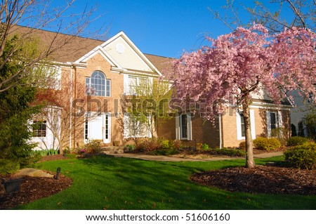 A beautiful home in the early morning light of spring with flowering cherry tree - stock photo