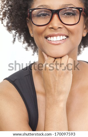 A beautiful intelligent mixed race African American girl or young woman looking happy and wearing geek glasses - stock photo