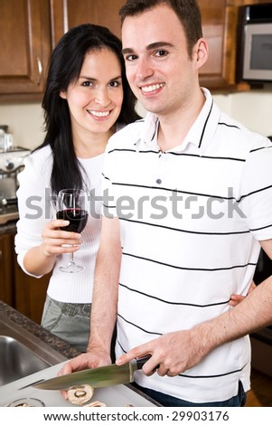 A beautiful interracial couple preparing food in the kitchen - stock photo
