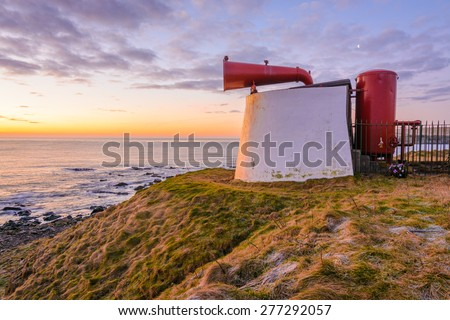 A Beautiful Isolated seascape with bright red fog horn on the Coastline of Aberdeen early on a March morning - stock photo
