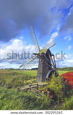 A Beautiful isolated windmill with white sails in open countryside under a stormy blue sky, Suffolk, United Kingdom  - stock photo