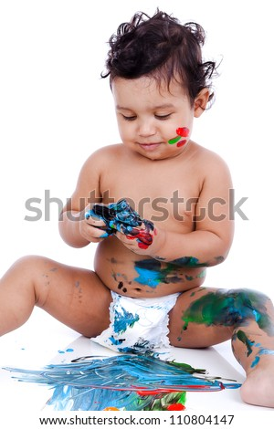A beautiful kid playing with his paints. The inky boy is busy with his paintings. The toddler is wearing diaper. - stock photo