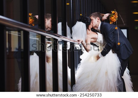 A beautiful kiss of a young newlywed couple near a mirror wall. - stock photo