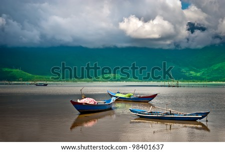 A beautiful lake view with three wooden boats under a dramatic sky - stock photo