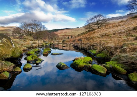 A beautiful landscape with blue sky and green stones in the foreground. This landscape is near dovestone reservoir in the Peak District, England. - stock photo