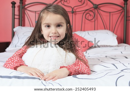 A Beautiful little girl on her bedroom - stock photo