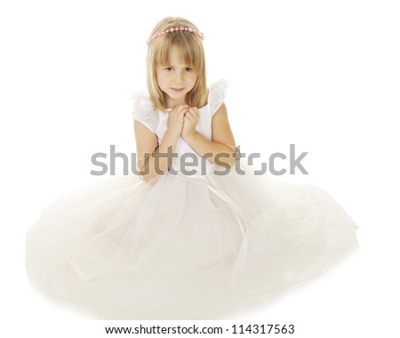 A beautiful little girl sitting in a flowing white dress and a halo of pink beads.  Her hands are clasped as she looks downward.  On a white background. - stock photo
