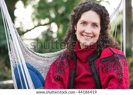 A beautiful mature woman sitting on a hammock - stock photo