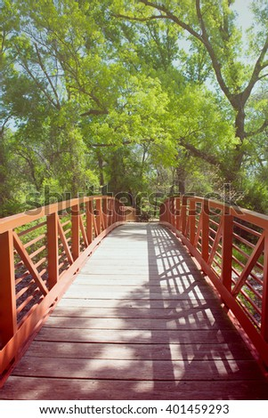 A beautiful metal bridge in jungle with lovely green background, filtered color tone - stock photo