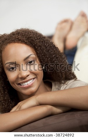 A beautiful mixed race African American girl laying down with perfect teeth and smile - stock photo