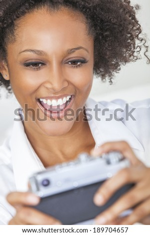 A beautiful mixed race African American girl or young woman laughing and taking a selfie picture on a retro style digital camera - stock photo