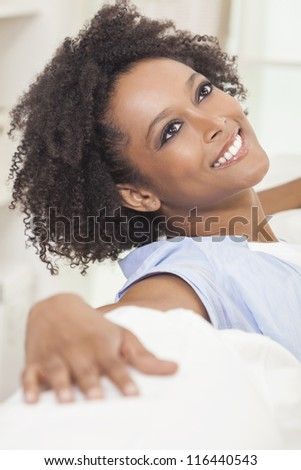 A beautiful mixed race African American girl or young woman sitting on sofa at home looking happy and relaxed - stock photo