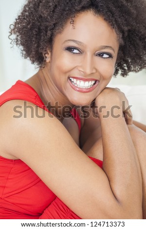 A beautiful mixed race African American girl or young woman wearing a red dress looking happy and smiling with perfect teeth - stock photo